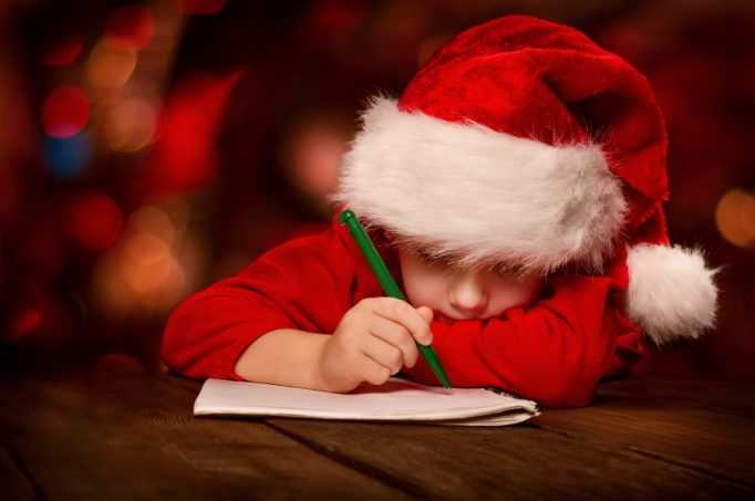 Christmas child writing letter to Santa letter over abstract bac